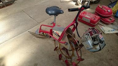 田んぼの中を走る小さなバイクは溝切り機